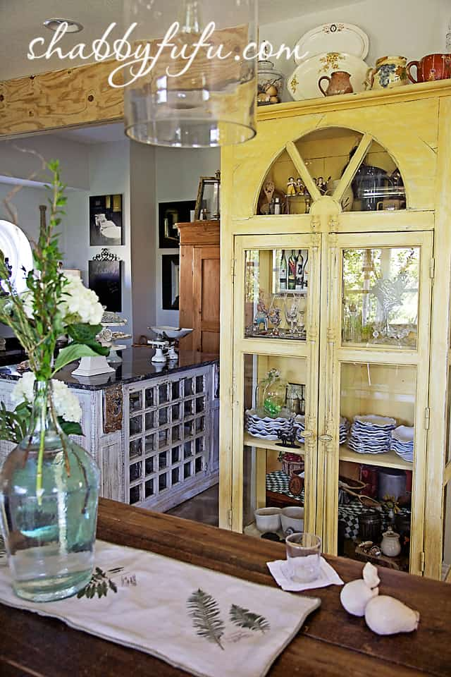 French country decor in Texas - restored wood china cabinet painted yellow