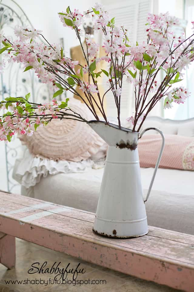 Faux pink blossoms in a rusted vintage water can match the aged paint on our vintage pink linen cabinet