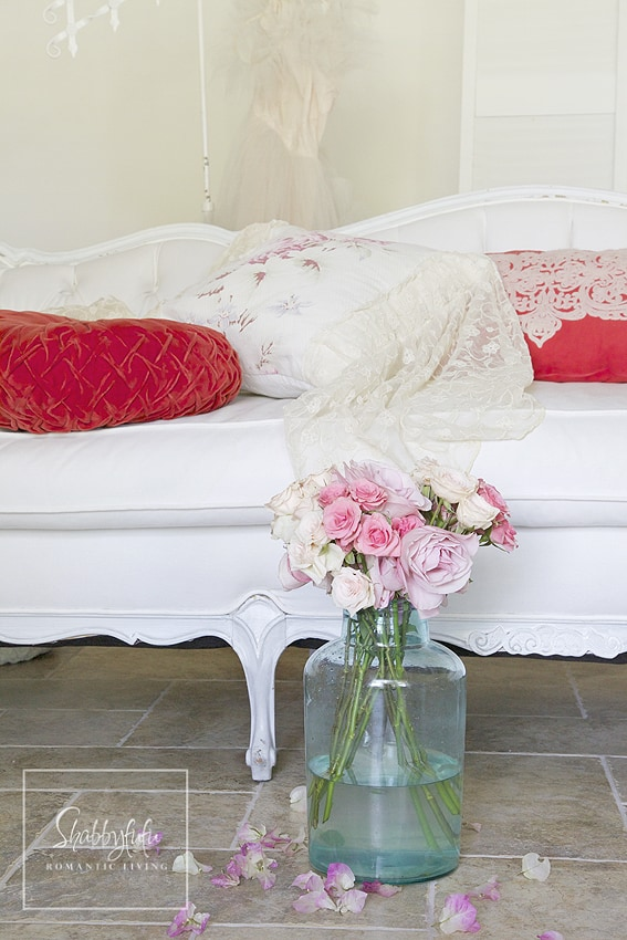 mix and match throw pillows by combining textures and colors that go with your decor. Here are some bright red throw pillows mixed with some light white, soft fabrics.