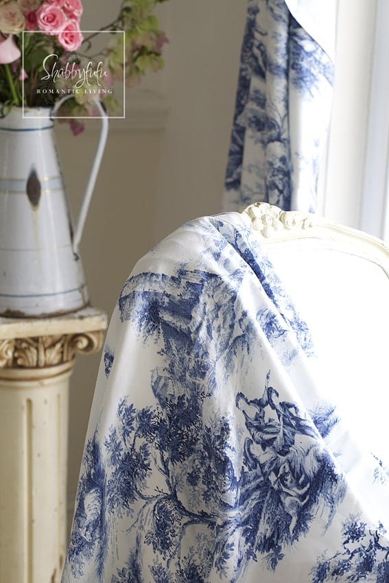 Decorating with toile - drapes of toile cover a neutral off-white chair