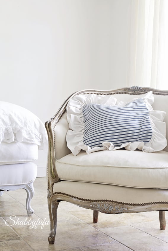 French farmhouse style sattine with white fabric and a blue and white striped throw pillow.