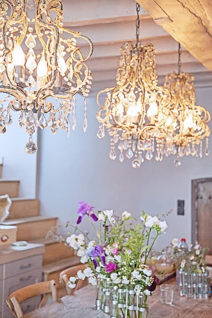 These French farmhouse style chandeliers are made with bright crystal and hang above a beautiful floral tablescape.
