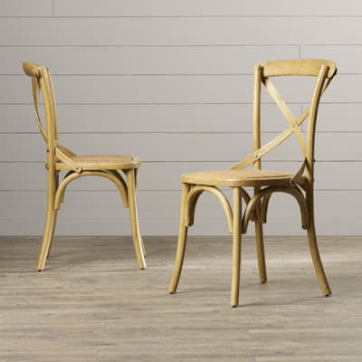Two French farmhouse style wooden dining room chairs.