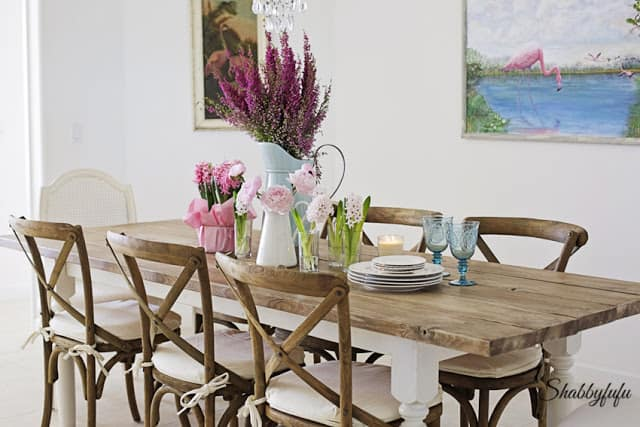 This French farmhouse style table scape is complete with dark wood chairs with white linen cushions, a beautiful pink flower centerpiece and beautiful wooden farmhouse dining table.