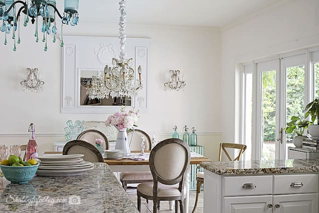 My French farmhouse style dining area; marble counter tops and a french style dining table with white linen chairs, an aqua blue crystal chandelier, and white walls.