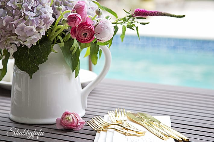 porch table setting with flowers and gold flatware