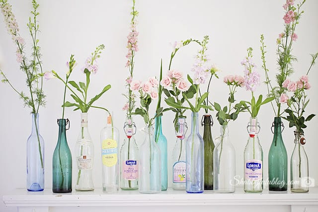 bottles on a mantel with flowers