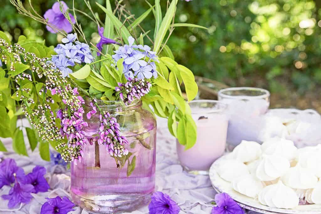purple glass jar with flowers on a table