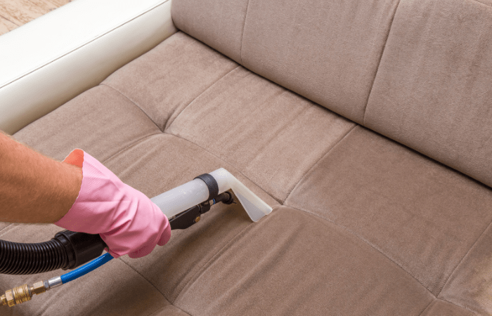hand-vacuuming-brown-couch