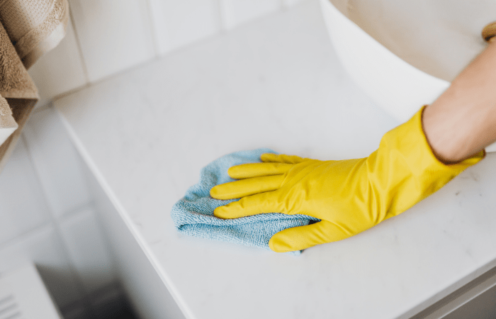 hands-with-yellow-gloves-cleaning-surface