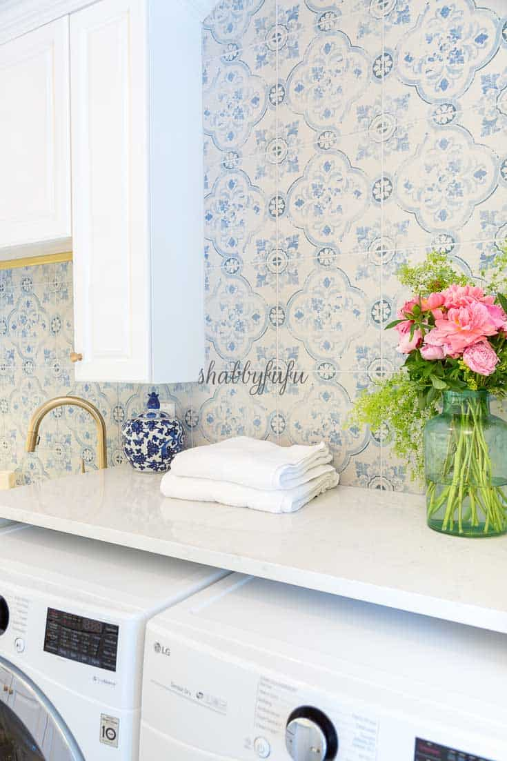 stylish functional laundry room with blue encaustic wall tile
