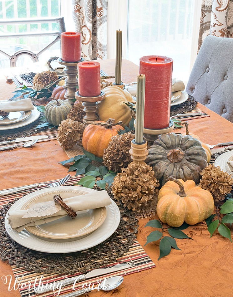 Thanksgiving table wet with pumpkins running the length as the centerpiece