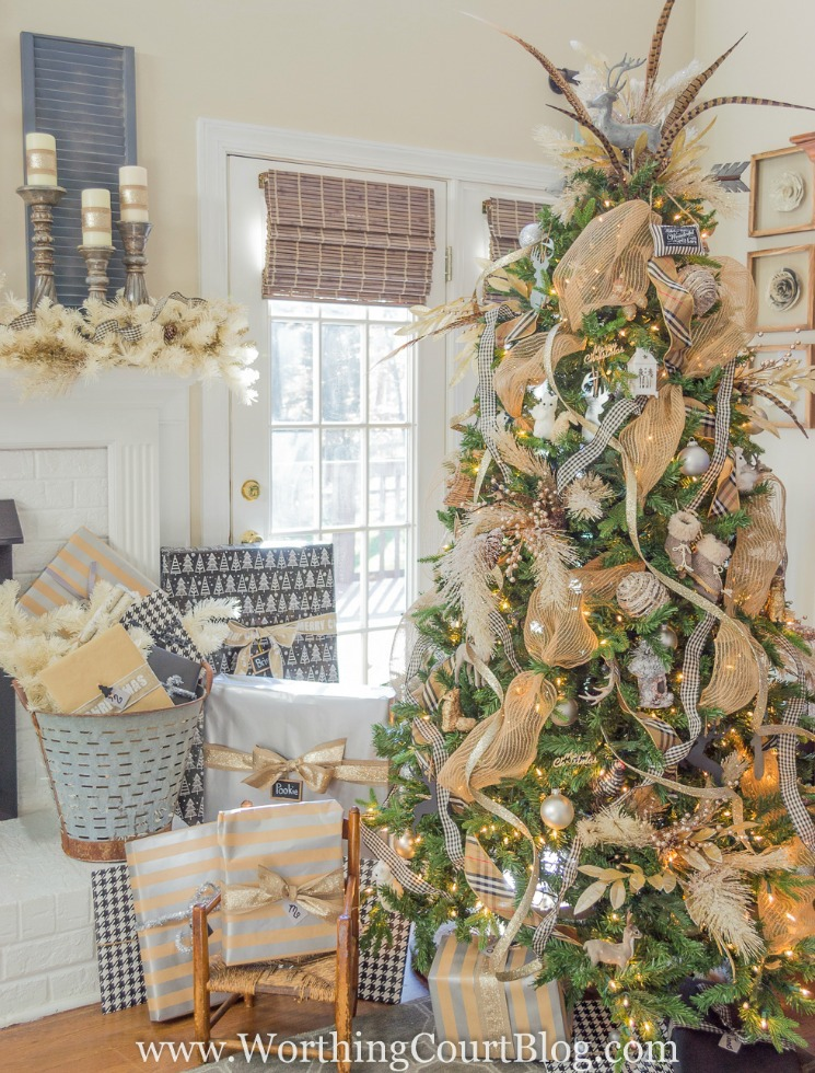 gorgeous Christmas tree decorated with gold ribbon and feathers beside a white brick fireplace