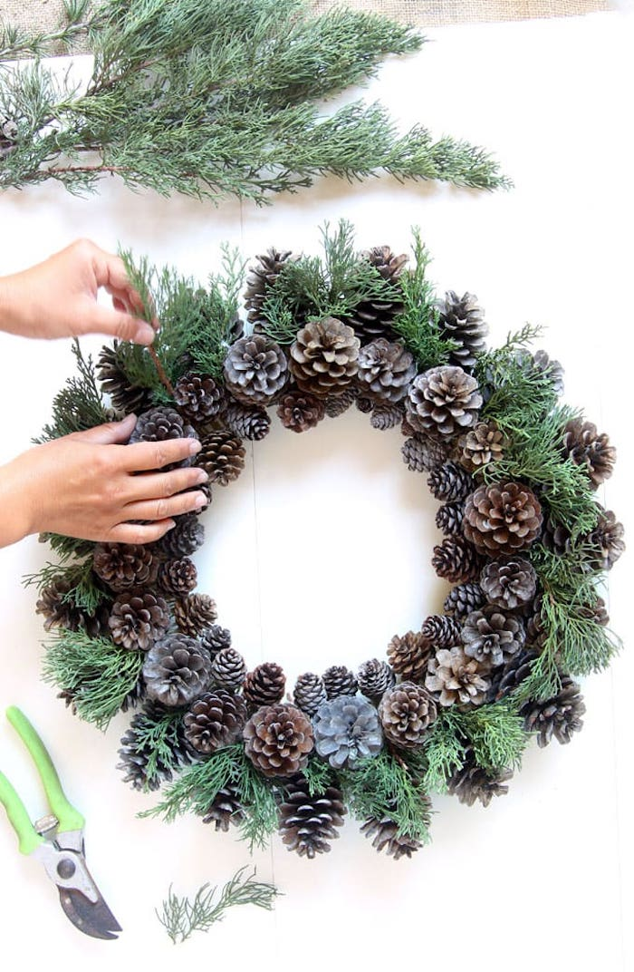 making a pinecone and evergreen wreath