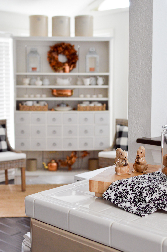 white hutch decorated for fall in the foreground of a kitchen