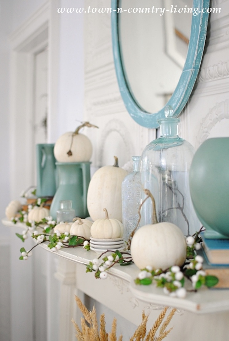 fall mantel with white pumpkins and vintage blue pottery