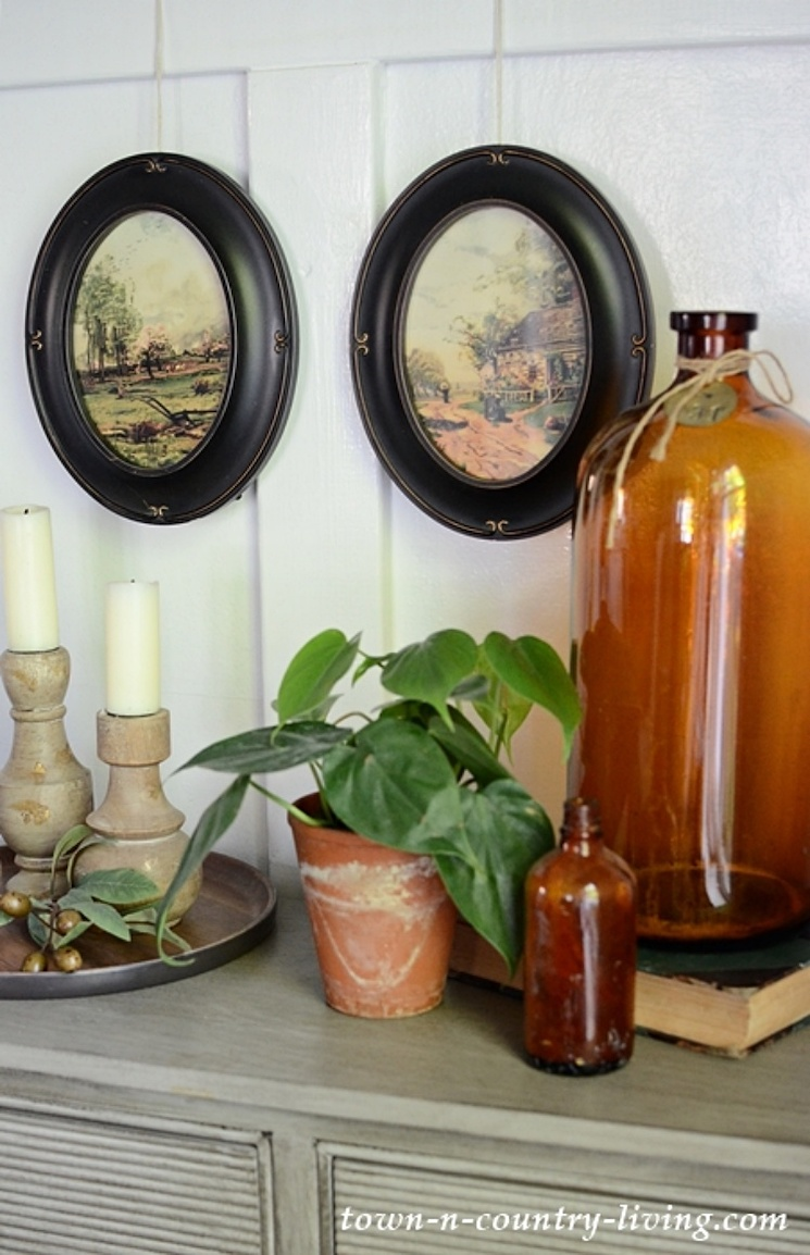 fall vignette with amber glass bottles, a houseplant, candlesticks and two oval framed landscape prints
