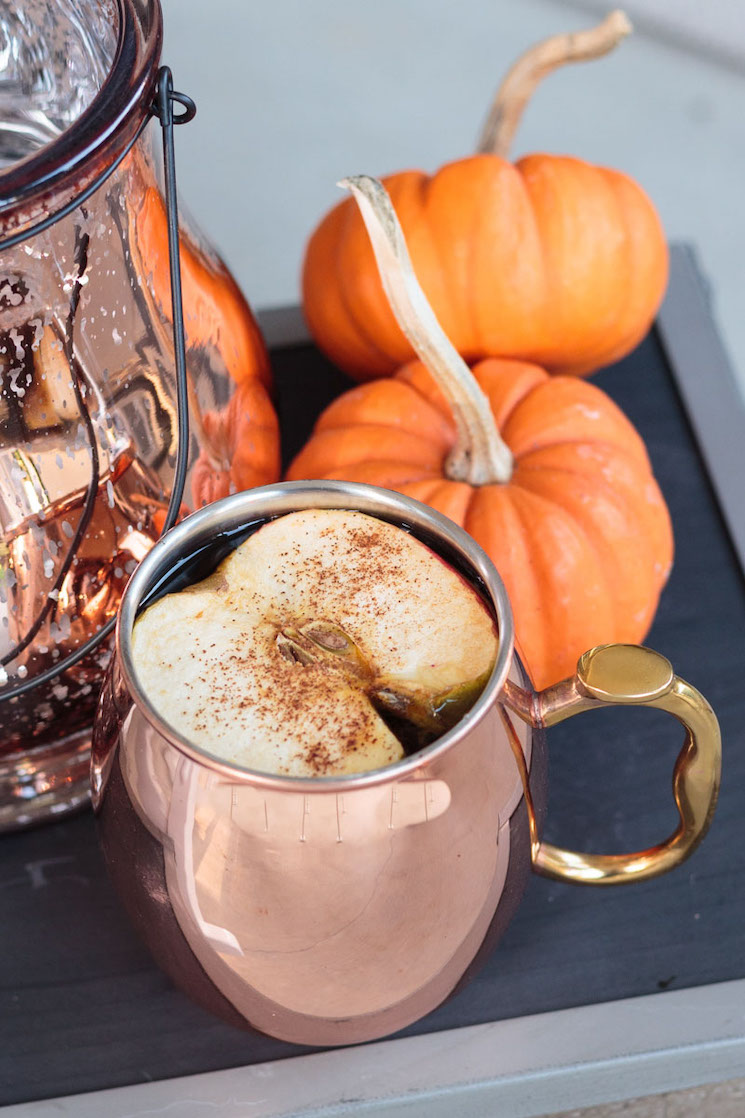 apple cider in a copper Moscow mule mug beside mini pumpkins on an overturned crate