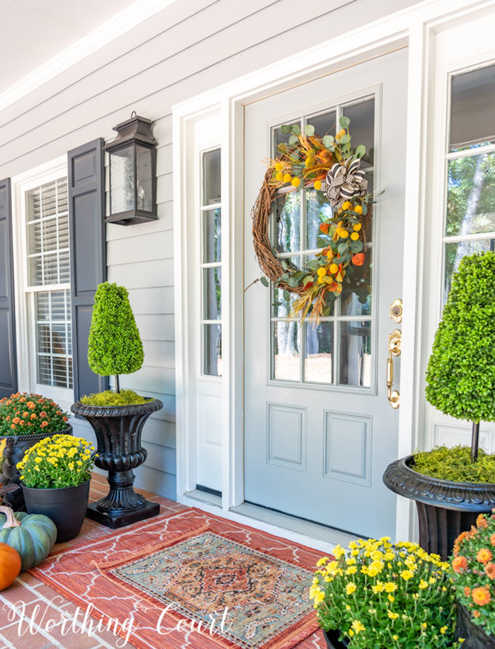 pretty fall front porch with a blue front door and topiaries