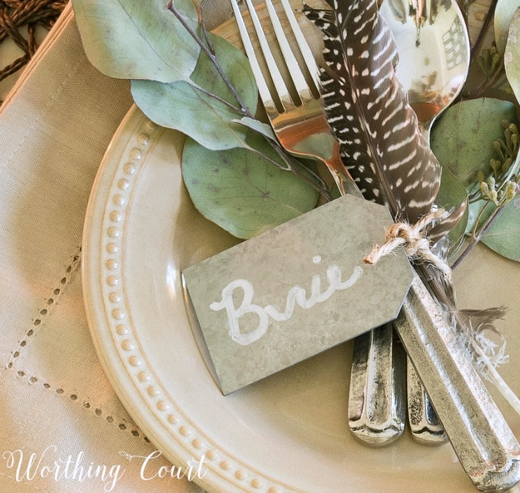 galvanized tag tied to silverware with a feather and eucalytus
