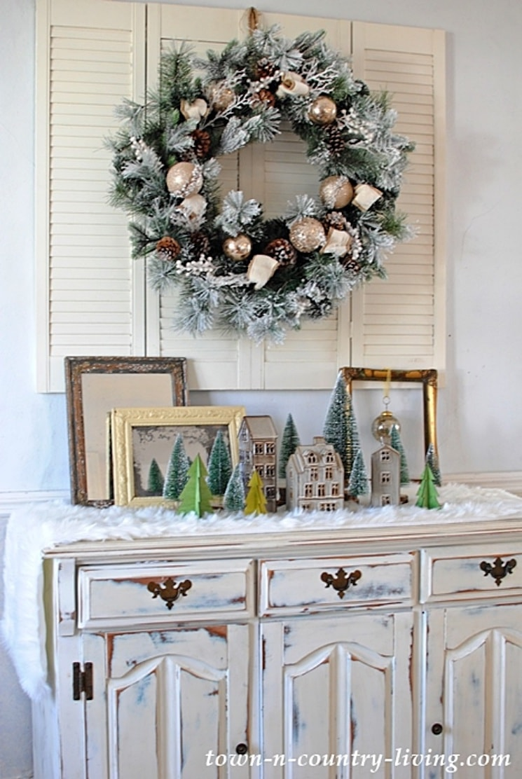 wreath hanging on shutters above a dresser decorated for Christmas