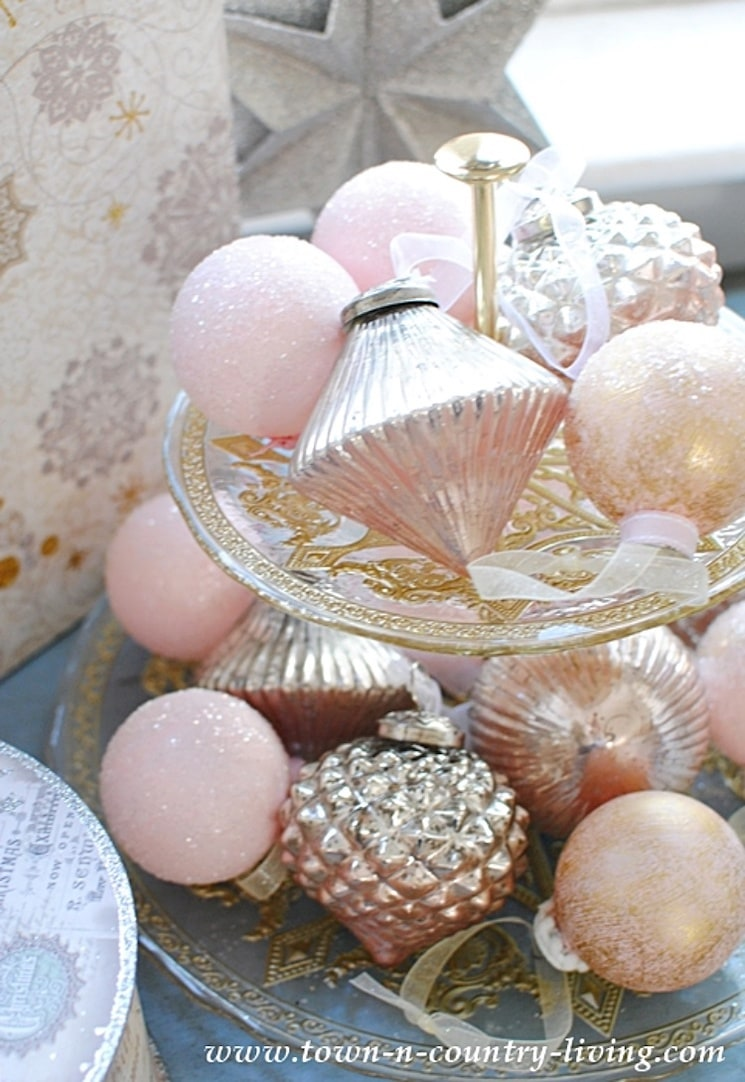 pink and gold Christmas ornaments on a tiered tray