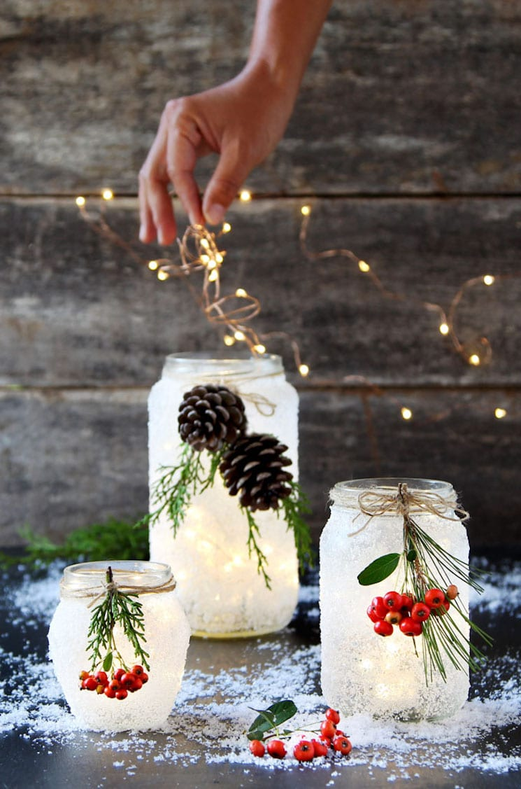 frosted mason jars decorated with Christmas greenery and berries
