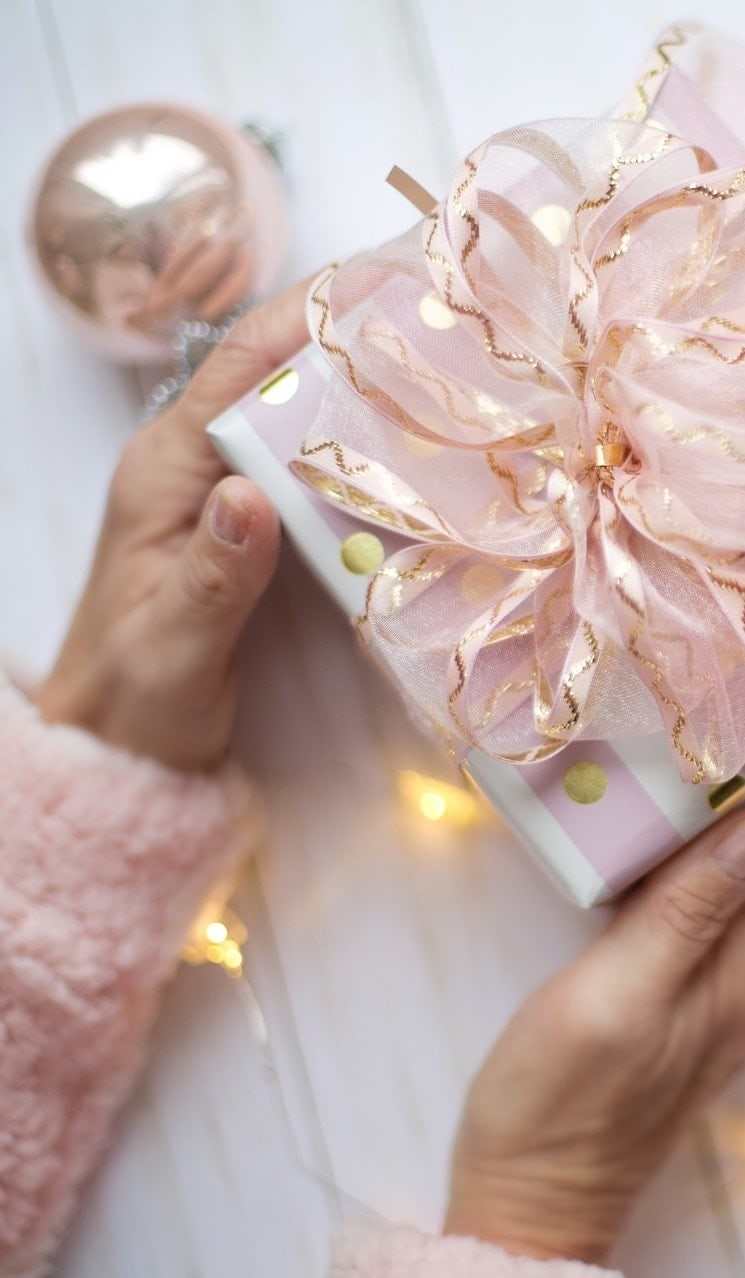 hands holding a Christmas present wrapped with pink paper and a bow