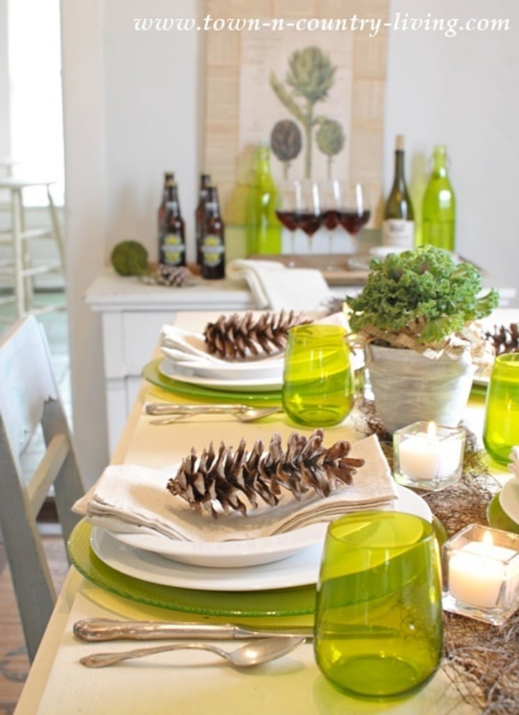 Thanksgiving tablesetting with green glassware and pinecones on each plate