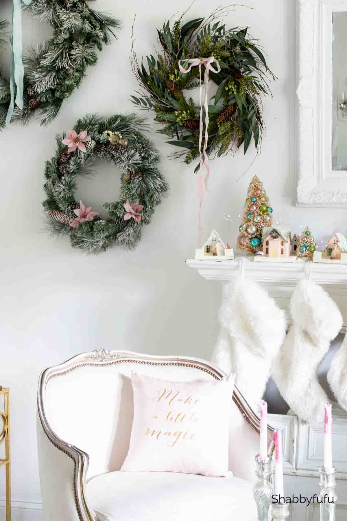 three Christmas wreaths hanging beside a mantel decorated with bottlebrush trees and paper houses