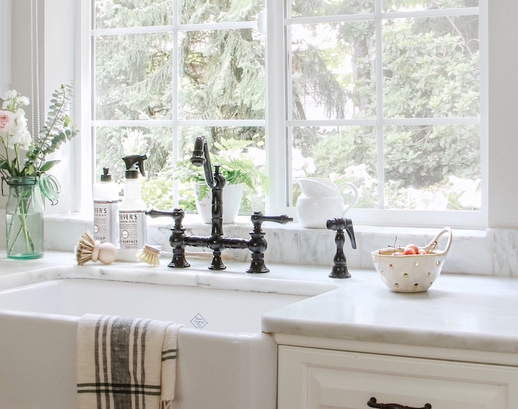white farm sink with a black bridge faucet