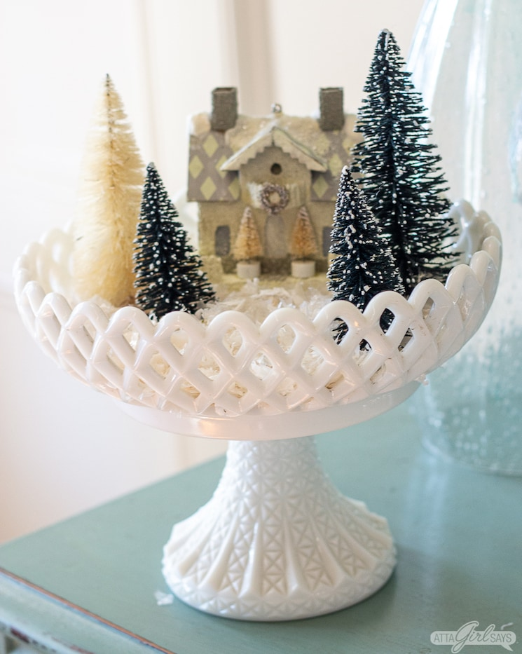 bottlebrush Christmas trees and a paper house displayed in a milk glass compote for Christmas