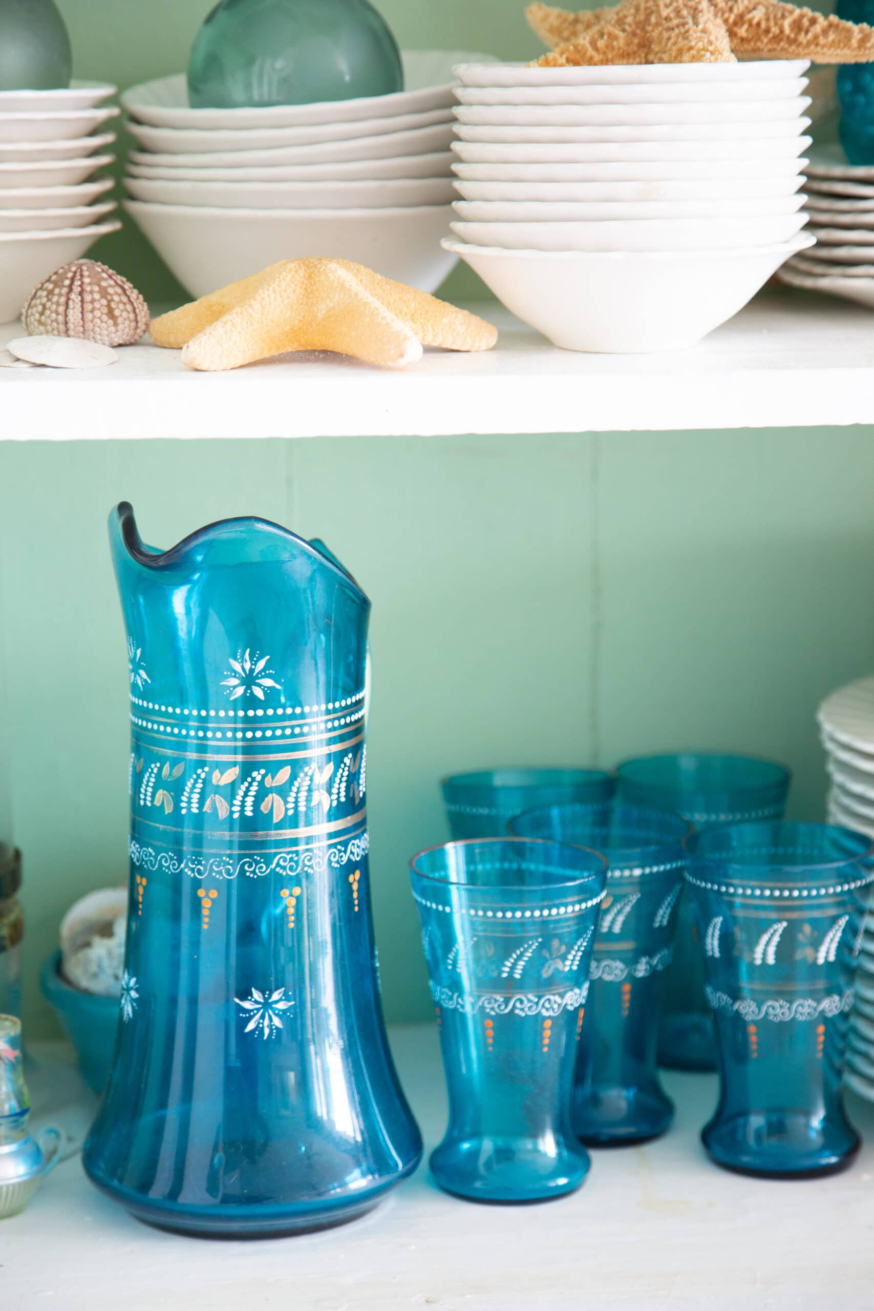 blue pitcher and glasses and stacked white dishes