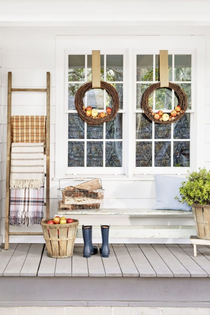 two windows with fall wreaths and a ladder holding blankets