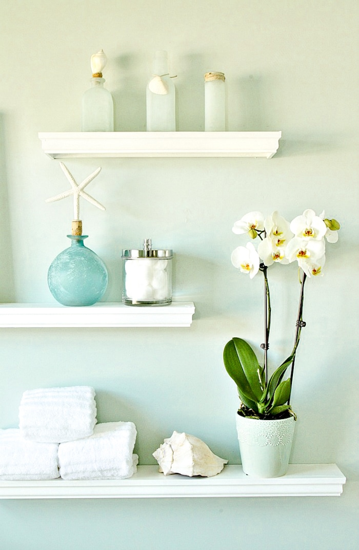 3 floating shelves on a wall with accessories