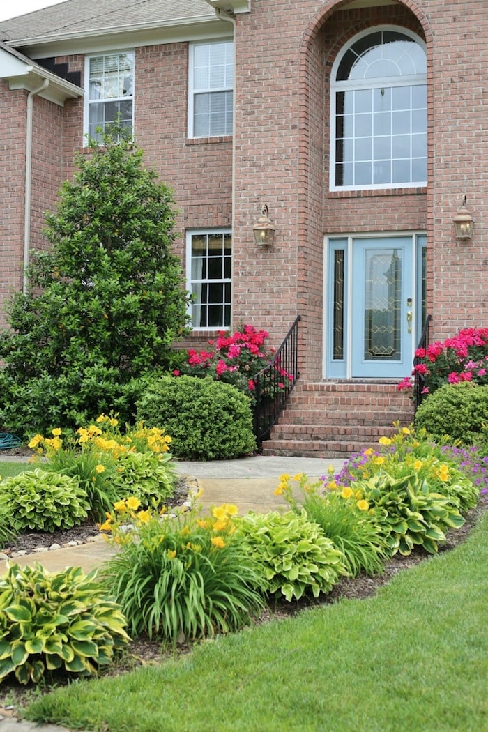 two story brick home front entrance and landscaping