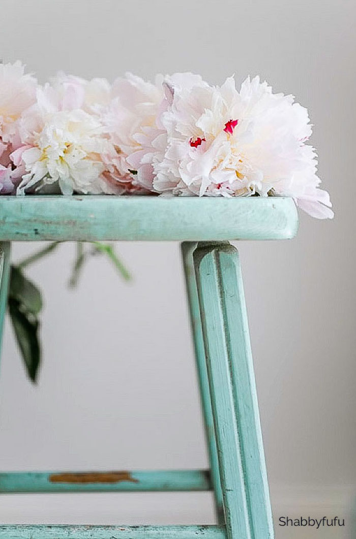 aqua color stool with flowers lying on top