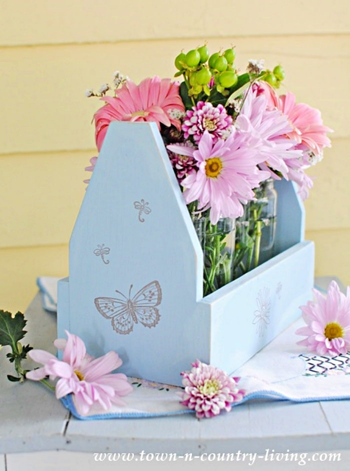 blue wooden tote filled with jars full of summer flowers