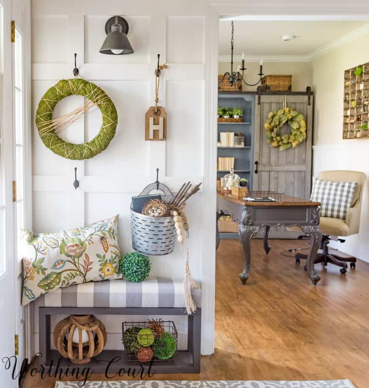 foyer wall with doorway looking into home office with decor