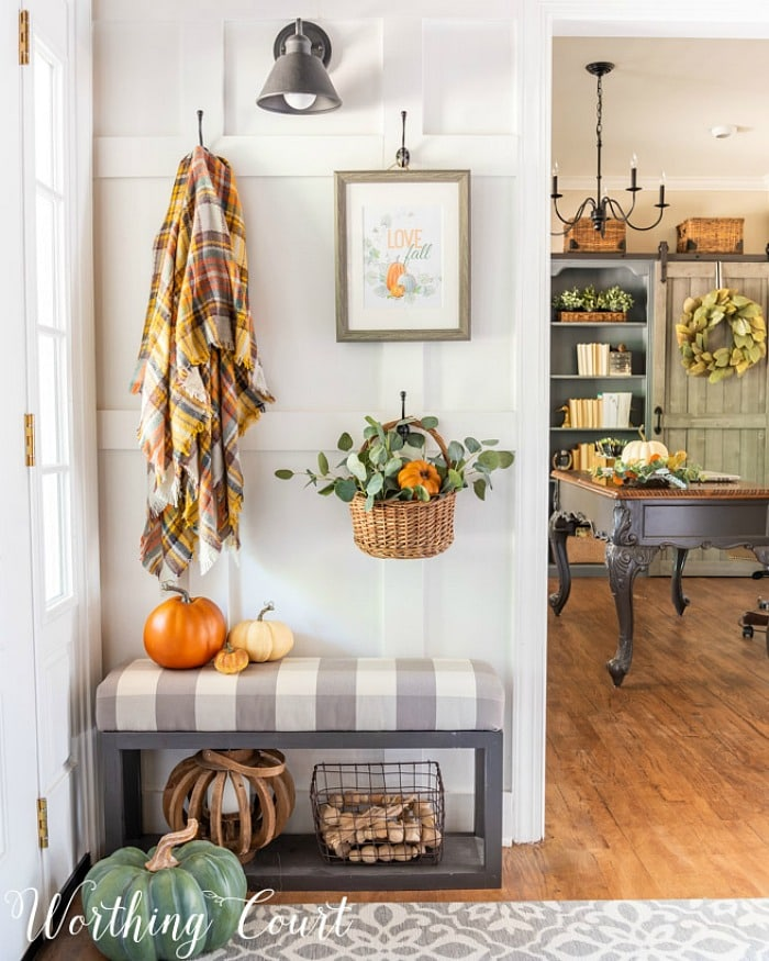 board and batten wall with fall decor hanging from hooks