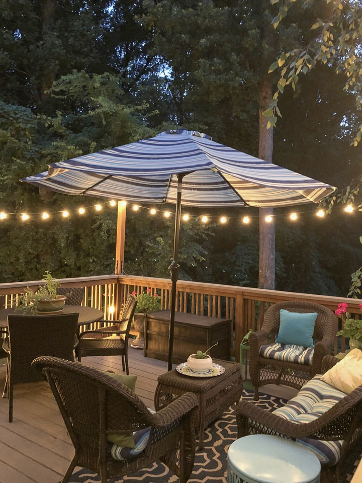 deck at night with string lights umbrella and furniture