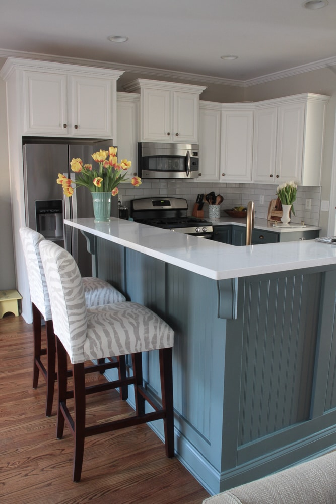 kitchen with white cabinets and blue island with stools