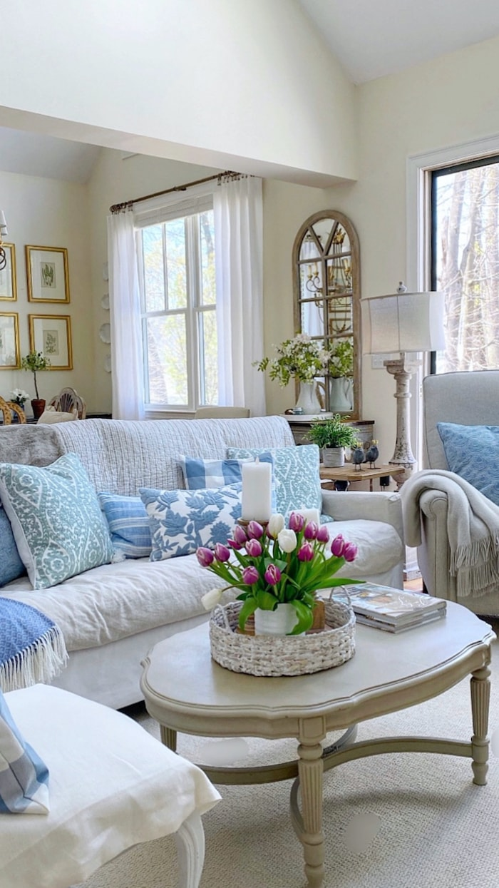 living room with white sofa, blue pillows and gray coffee table