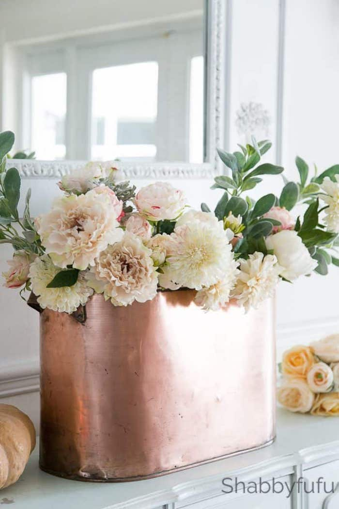copper container filled with white flowers