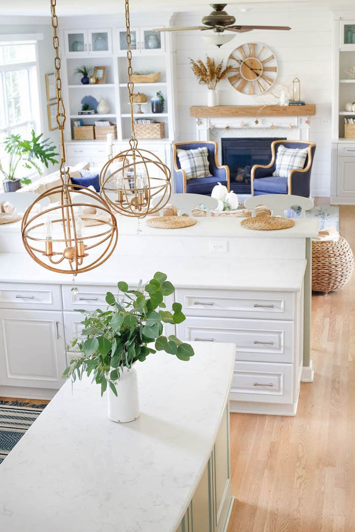 navy chairs in from of white fireplace and white kitchen cabinets