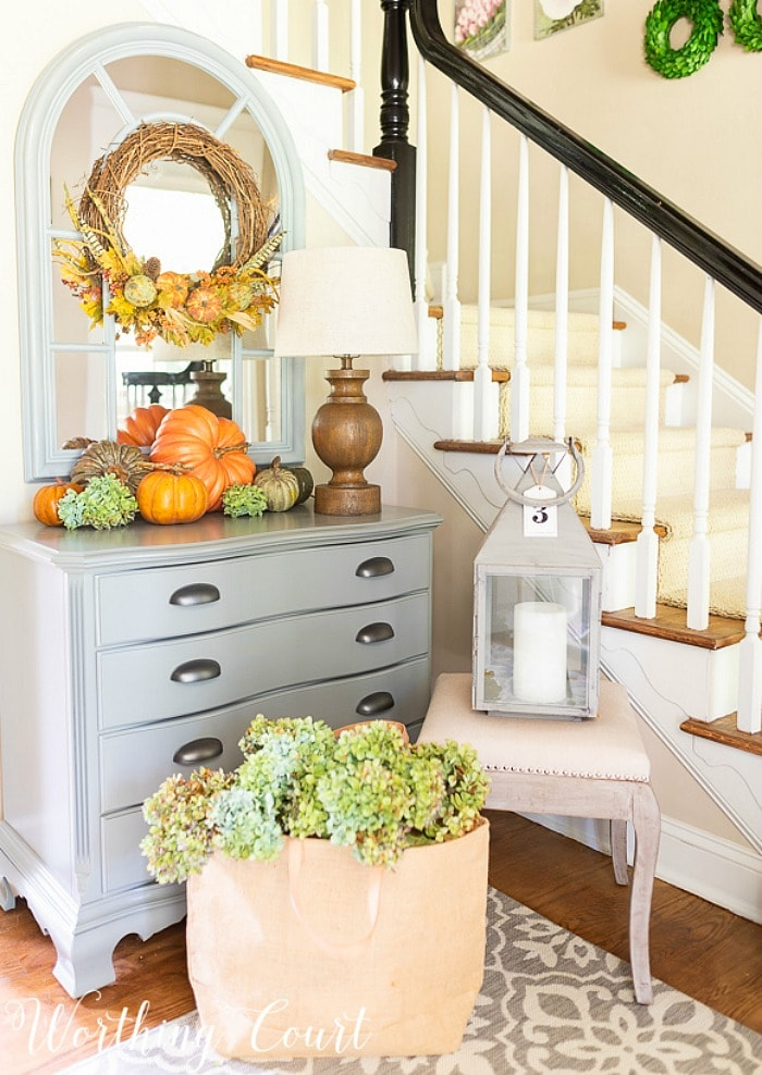 foyer with gray chest arched mirror and fall decorations