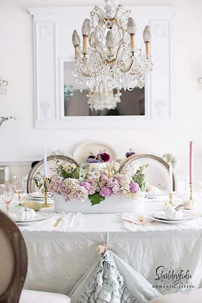 white dining room walls and white linens with a fall centerpiece