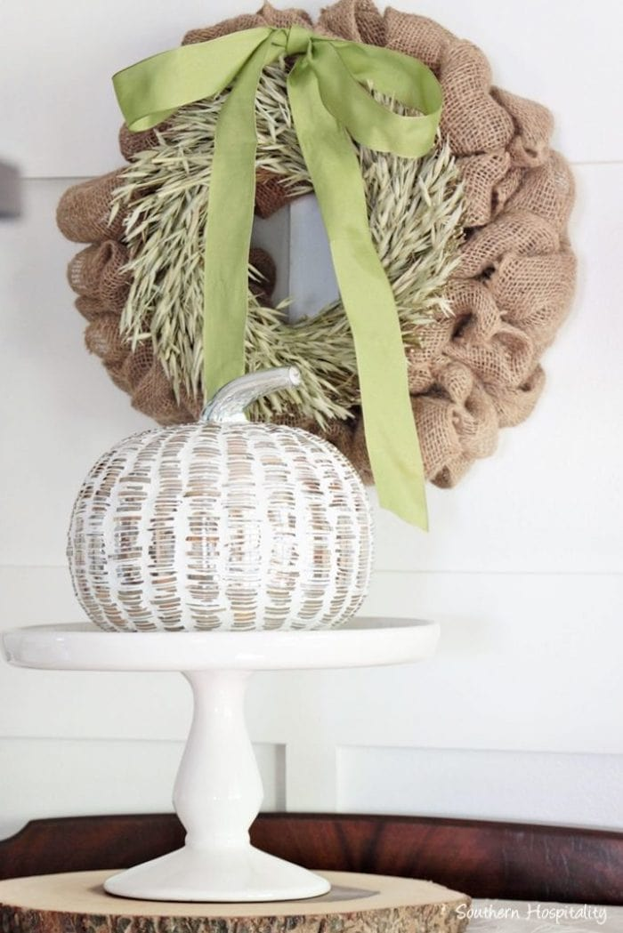 burlap wreath with a green bow and wood-look pumpkin on a pedestal