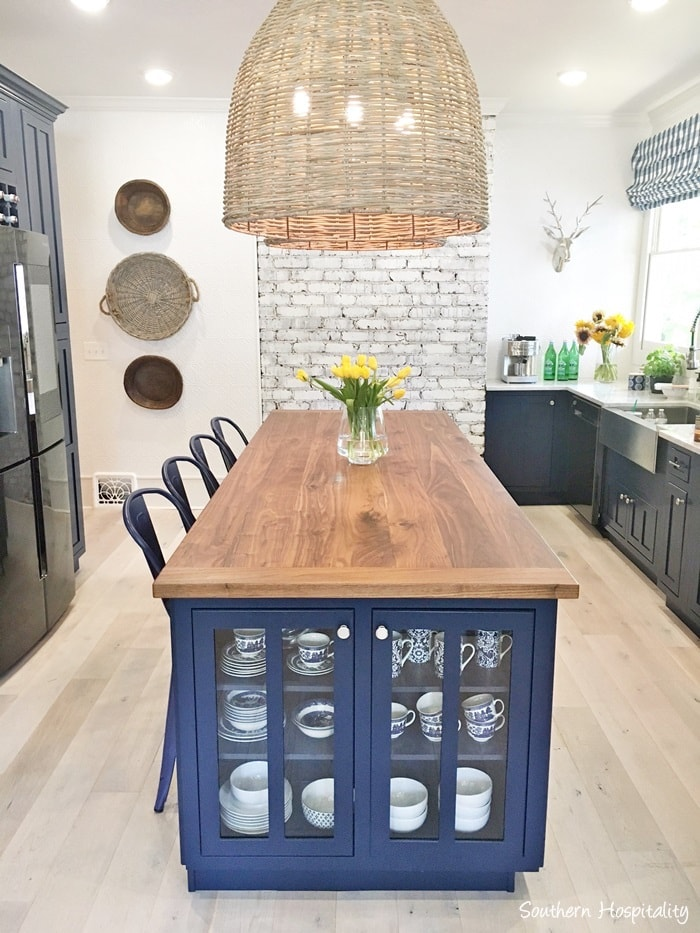 navy blue kitchen island with cabinet on end and wicker pendants above