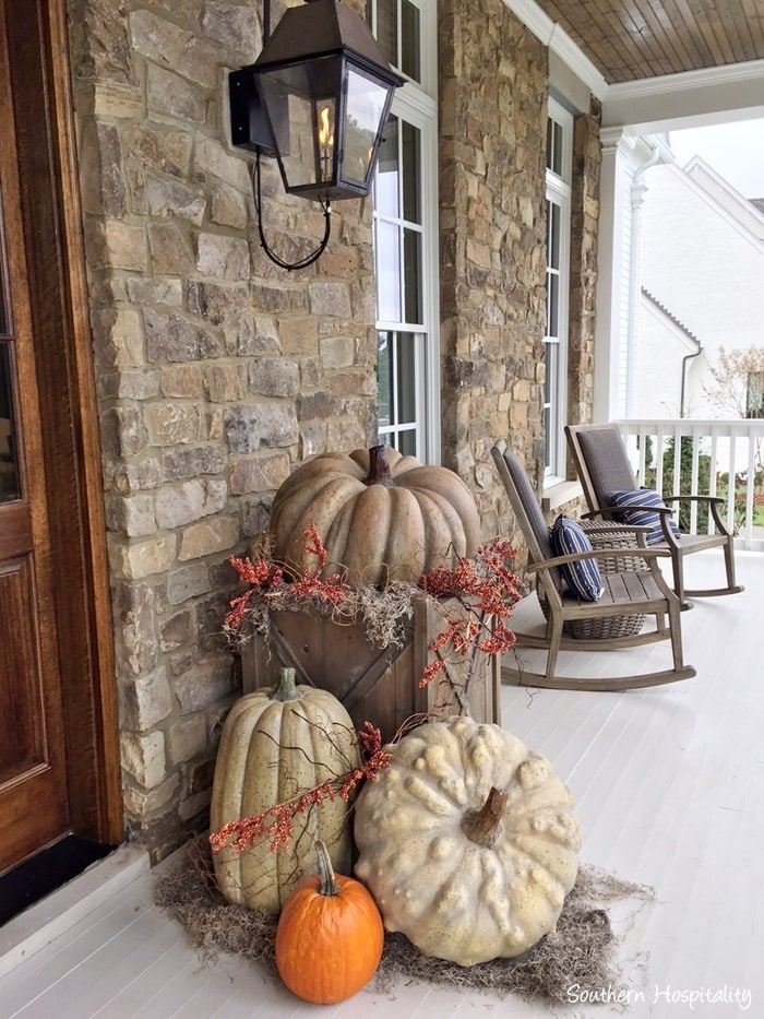 front porch with stone wall and rustic pumpkins in a wooden planter